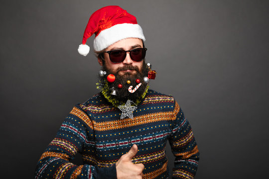 Bearded male in santa hat shows thumbs up.