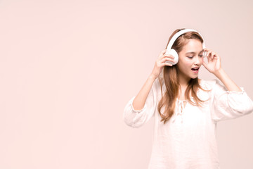 young girl wearing wireless headphones, listening a music and singing