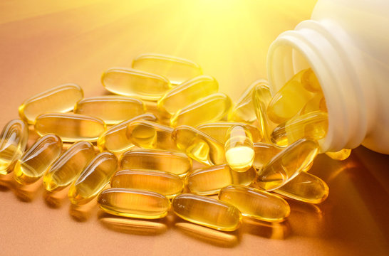 Fish oil capsules with omega 3 and vitamin D in a plastic bottle on a shiny texture with sun beams, healthy diet concept