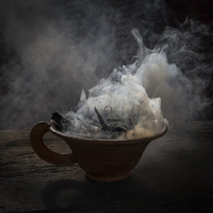 Steaming clay cup with spices on wooden table in street. Still life black background, Nepal.