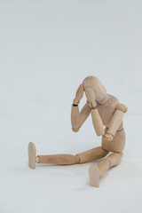 Tensed wooden figurine sitting with hands on head