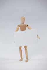 Wooden figurine standing and holding a white placard