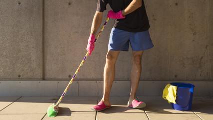 Ein Hausmann in rosaroten Hausschuhen wischt den Boden mit einem bunten Besen