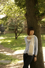 Young woman leaning against tree