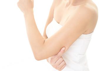 二の腕をつまむ女性