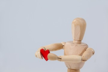 Wooden figurine holding a red heart in front