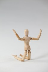 Wooden figurine kneeling with arms spread wide