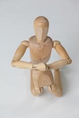 Wooden figurine kneeling with both hands joined