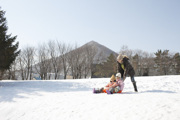 Father and children at play sledding