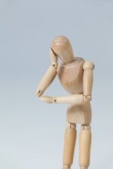 Thoughtful wooden figurine pretending to lean