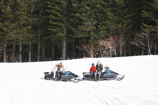 Family riding on snowmobiles