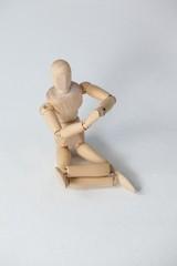 Wooden figurine performing yoga on floor