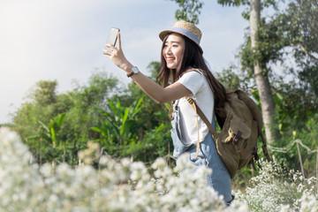 Asian teen woman takes a selfie in whote flowers garden, wearing
