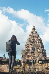 Rear view of young attractive woman tourist with backpack.