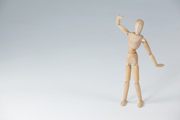 Wooden figurine standing with hand raised