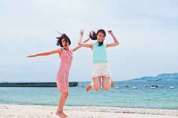 Two women jumping on the sandy beach
