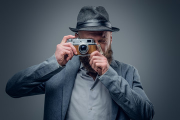 A man shooting with the vintage SLR photo camera.
