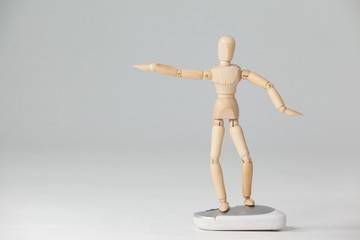 Wooden figurine standing with arms spread on a mouse