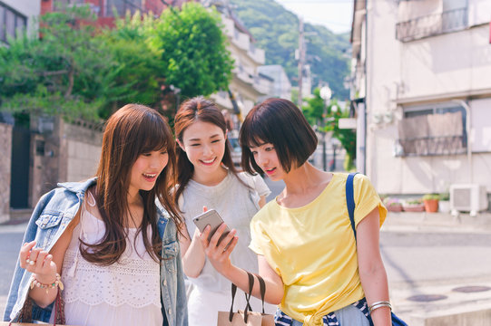 Three woman looking for the shop by using smart phone