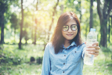beautiful girl drinks water from a bottle on the nature