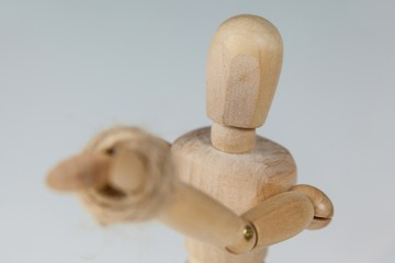 Hands of wooden figurine tied with a rope