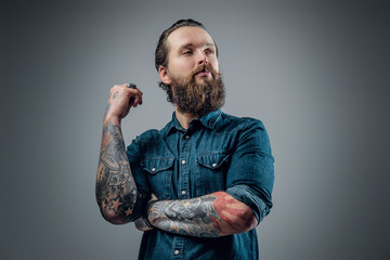 Bearded man with tattoos on arms.