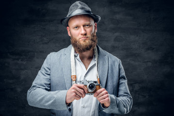 Bearded male holds vintage slr photo camera.