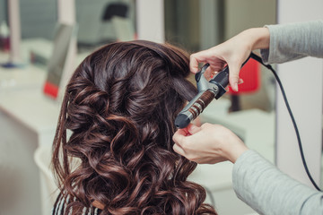 Hairdresser doing wrap curling brunette hair in a beauty salon with iron
