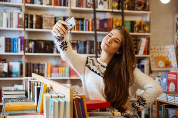 Pretty young woman taking selfie with mobile phone in library