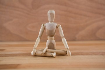 Wooden figurine sitting in a lotus position