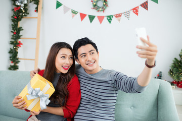 Christmas Asian Couple. A handsome man giving her girlfriend/wif