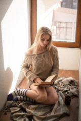 Young beautiful woman in a sweater reading a book.