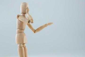 Wooden figurine applying makeup