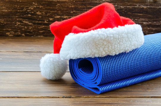 Close up of blue mat with Santa Clause hat on wooden background. Best Christmas gift for active person. Yoga xmas concept.  Copy space.