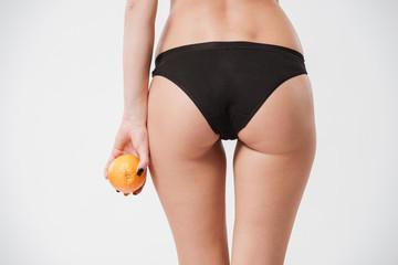 Female ass in black panties holding orange