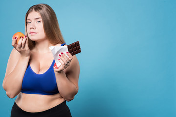 Pretty plump girl holding chocolate and apple