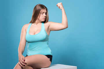 Chubby woman looking at her biceps