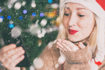 holidays, winter and people concept. happy young woman wearing a santa claus hat at home, next to a christmas tree. alternative hipster girl sending kisses over a video call on her smartphone.