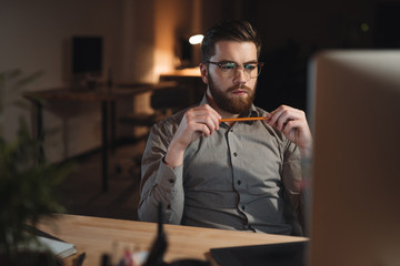 Concentrated bearded web designer working late at night