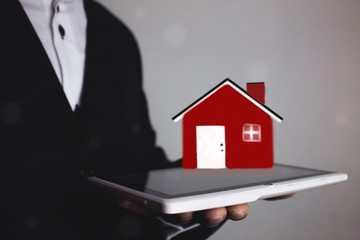 man holding tablet and house
