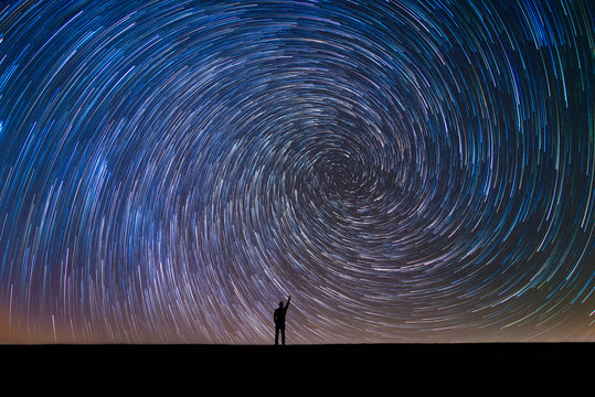 Silhouette of a man pointing at the north star vortex star trail