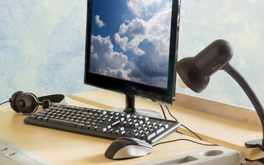 Monitor, keyboard, mouse, headphones and light fixture on a desk