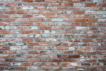 Orange brick wall, weathered and aged siding