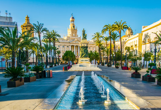 View of a fountain situated on the square of saint john of god in cadiz with town hall on background