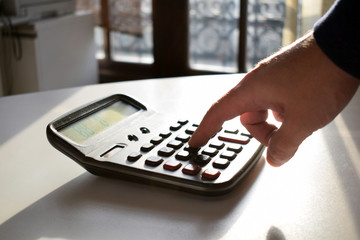 Businessperson working in office.Man hand with calculator at work