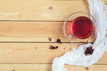 Cup of red hot tea and dry tea in wooden spoon on light wooden table, top view