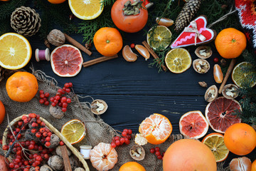 Christmas Wallpaper with tangerines, oranges, nuts, grapefruit, kiwi, persimmons, cinnamon, cranberry, gingerbread and Christmas tree branches with cones on a wooden black background