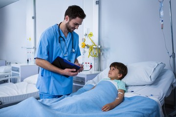 Male nurse interacting with patient during visit in ward