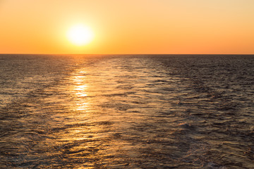 Wake of the cargo ship at sunset time.