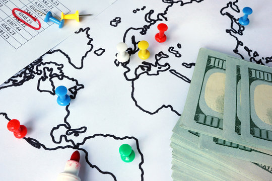 Thumb tacks in a world map and cash. Anti-money laundering (AML) concept